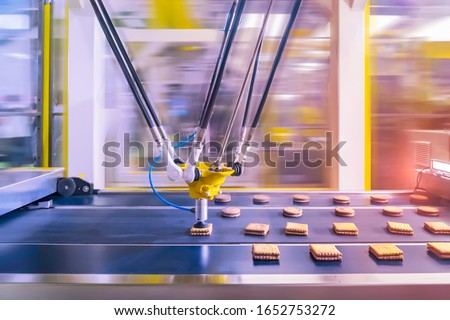 robot with vacuum suckers with conveyor in Production of cookies in a manufacture factory for the food industry Foto stock ©