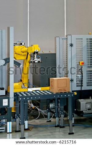 Robotic arm at work in factory packing boxes