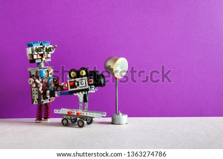 Robotic filmmaking. Funny robot cameraman operator shoots television movie or motion picture. Automated process of creating video content. Purple wall studio background
