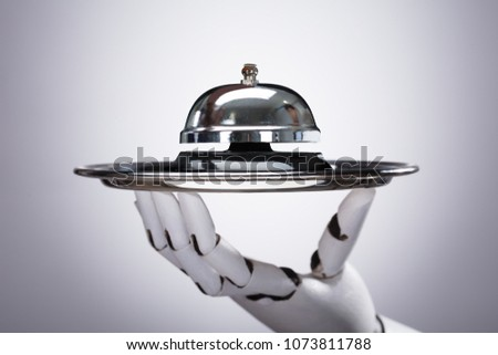 Robotic Hand Holding Service Bell In Plate Against Grey Background