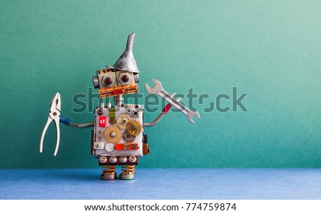 Robotic handyman pliers hand wrench. Fixing maintenance concept. Creative design toy with metal funnel hopper, cogs wheels gears silver metallic body. Green wall, blue floor background. Copy space