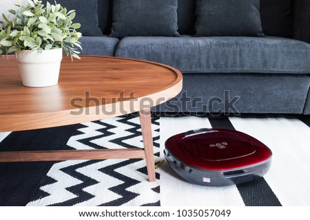 Robotic vacuum cleaner on carpet  in cozy living room with navy blue sofa and wooden table - Shutterstock ID 1035057049