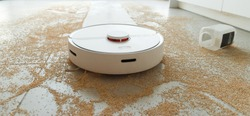 Robotic vacuum cleaner on tile floor full of grains. Smart cleaning technology for human faults .