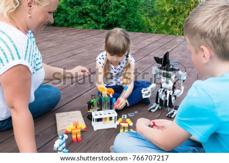Robotics class in summer in the open air. The teacher explains the lesson to the girl and   boy. Lego robot, Mindstorms, EV 3, tubes, microscope. Stem education. Minsk, Belarus - August, 2017.