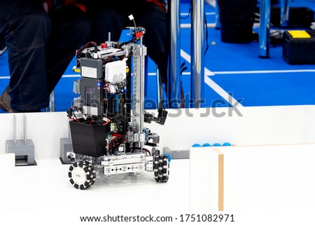 Robotics. Demonstration of the robot. Programmable robot on a white table. The robotics club. Writing programs for robots. Robotics competitions.