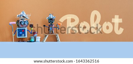 Robotics designers and artificial intelligence concept. Two painter artist robots decorated the wall in brown. The little robot painted the word Robot.