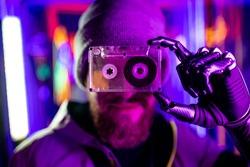 robotics man with metal hand nostalgia about past time in neon studio feeling loneliness hold audio tape cassette