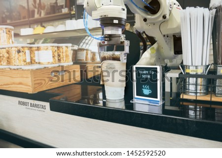 Robotics Trends technology in business. Autonomous machine learning robotic arms serves up a cup of coffee in cafe. Futuristic concept.