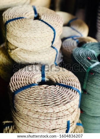 Robs for selling. Coiled rope at a fishing shop for fishing industry. A collection of  coiled rope. White coiled ropes, black coiled rope.