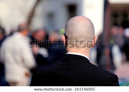 robust security guard with dark glasses and a radio headset to control people