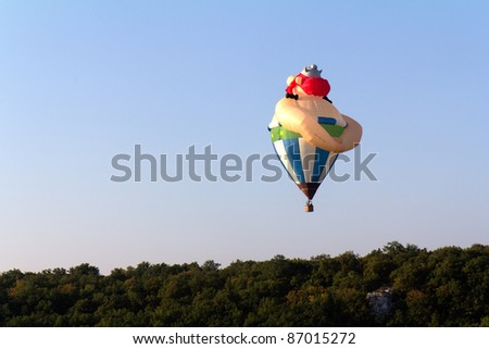 ROCAMADOUR, FRANCE- SEPTEMBER 25: Obelix hot air balloon ascending at sunrise for the 26ème Montgolfiades de Rocamadour, on September 25, 2011 in Rocamadour, France.