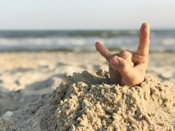 Rock and roll hand sign on a beach background. Human hand out of the hole on the sandy beach. Sea concept.
