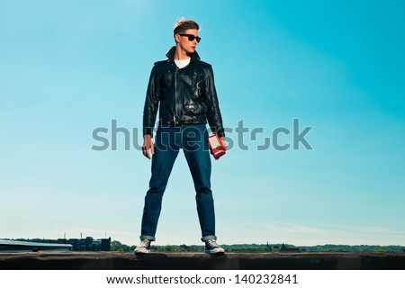 Rock and roll man 50s style with black jacket. Holding portable radio. On rooftop. Blue sky.