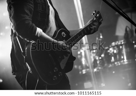 Rock and roll music black and white background, electric guitar player on a stage, photo with soft selective focus