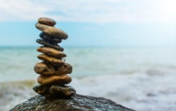 Rock balance. Stones placed one on top of the other, on the beach. The sea in the background