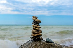 Rock balance. Stones placed one on top of the other, on the beach. The sea in the background. Concept - meditation, balance, patience, peace