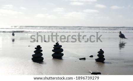 Photo of  Rock balancing on ocean beach, stones stacking by sea water waves. Pyramid of pebbles on sandy shore. Stable pile or heap in soft focus with bokeh, close up. Seamless looped cinemagraph. Zen balance.