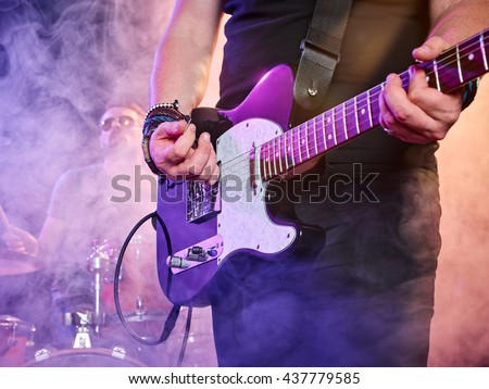 Rock band performs on stage. Guitarist, bass guitar and drums. Guitarist in the foreground. Close-up. #437779585