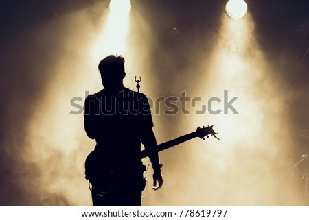 Rock band performs on stage. Guitarist plays solo. silhouette of guitar player in action on stage behind lights #778619797