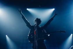 Rock band vocalist silhouette with the guitar singing to microphone with the hands raised up in blue lights