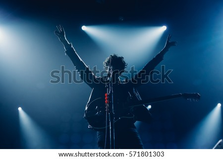 Rock band vocalist silhouette with the guitar singing to microphone with the hands raised up in blue lights #571801303