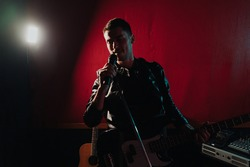 Rock band vocalist with the guitar singing to microphone in lights on red background