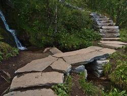 Rock bridge on hiking trail of stone material constructed by Nepali Sherpas leading to famous peak of mountain Reinebringen, Moskenesøya island, Lofoten, Norway with small waterfall and green plants.