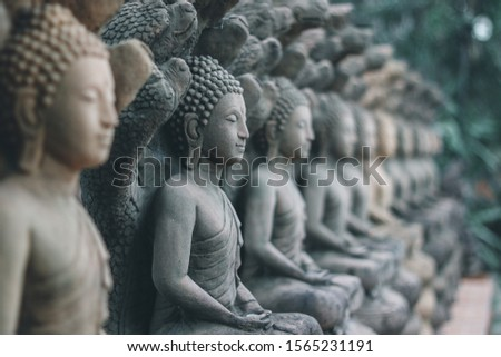 Rock Buddha statue with sunlight used for amulets of Buddhism religion. Buddhism is popular region in Thailand and south east Asia.