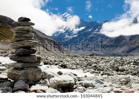 Rock cairn in Hooker Valley on a trail leading to Aoraki, Mount Cook, highest peak of Southern Alps, an icon of New Zealand partially covered in clouds