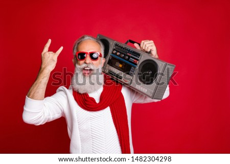 Rock chritmastime! Portrait of crazy santa in eyeglasses eyewear screaming showing swag sign holding boom box wearing white sweater isolated over red background