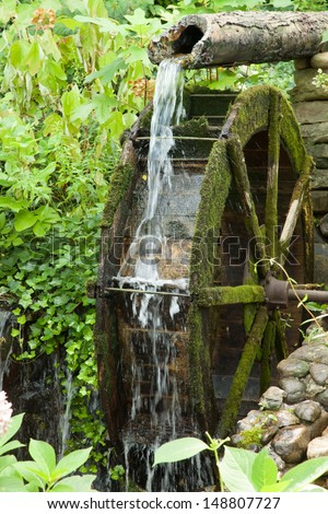Rock City, Lookout Mountain, Tennessee, USA, water from a broken pipe spilling on an old mill wheel, surrounded by bushes and green growth - stock photo