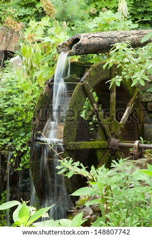 Rock City, Lookout Mountain, Tennessee, USA, water from a broken pipe spilling on an old mill wheel, surrounded by bushes and green growth