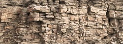 Rock cliff face background. Toned. Wild stone protruding crumbling layered blocks in quarry. Abstract texture for stone mining industry. Copy space for custom text. Front view