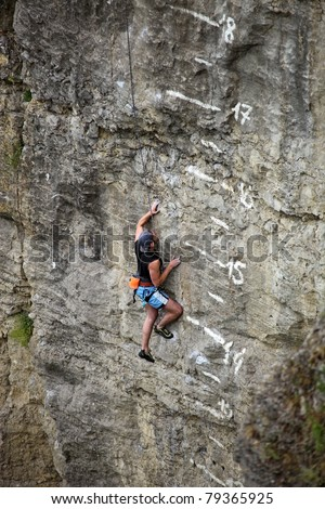 Rock climber battling his way up cliff