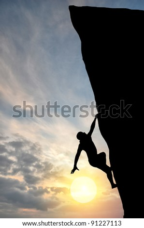 rock climber climbs the steep cliff to the top against the setting sun