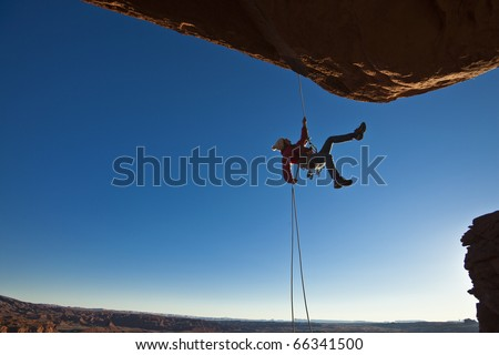 rock climber dangles in midair...