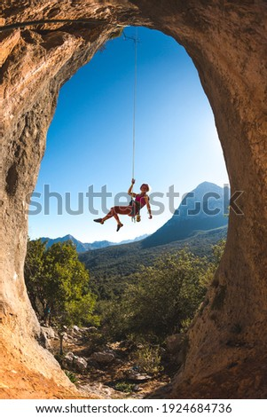 Rock climber descends from the route, the climber hangs on a rope, a rock in the form of an arch, climbing routes in a cave, a girl rides on a rope