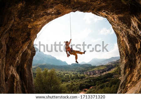 Rock climber hanging on a rope. A woman climbs a rock in the shape of an arch. The girl climbs in the cave. Climbing rope for belaying. Rock climbing in Turkey .