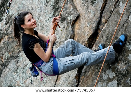Rock climber hanging on the rope - stock photo