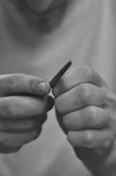 Rock climber is smoothening the skin of his hands with a file. Detail shot of his hands in Black and white.