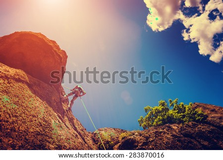 Rock climber on a cliff against the sky background. Vintage colors