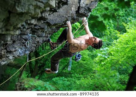 Rock climber on route, with bright green foliage in the background