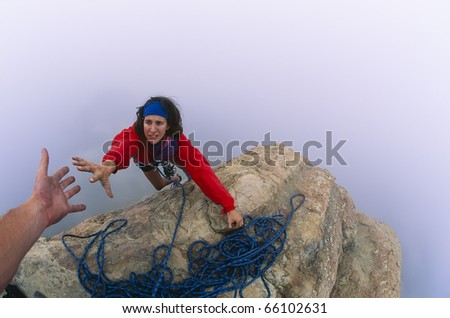 Rock climber on the summit reaching for a helping-hand from her partner.