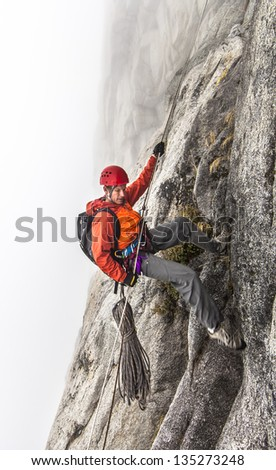 Rock climber rappels  on a challenging cliff.