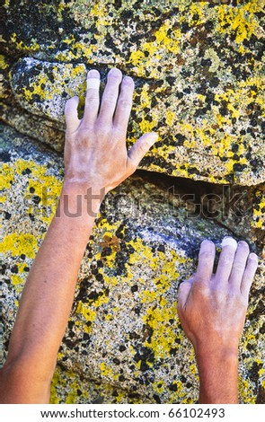 Rock climber reaching for the next hand hold on a steep wall.