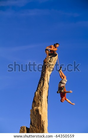 Rock climber rescues her partner on the edge of an overhanging pinnacle.