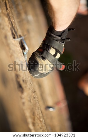 Rock climber's foot on rock - stock photo