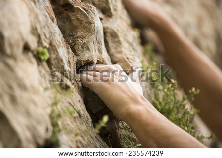 Rock climber\'s hand grasping handhold on natural cliff. His hand is covered in chalk. Shallow depth of field.