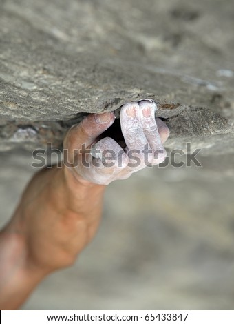 Rock climber's hand grasping handhold on natural cliff. His hand is covered in chalk. Shallow depth of field.