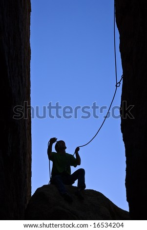 Rock climber silhouetted as he belays his partner up a chimney in Joshua Tree National Park.